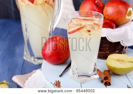 Glass and carafe of apple cider with fruits and spices on table close up