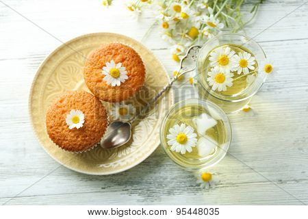Glasses of chamomile tea with chamomile flowers and tasty muffins on color wooden background