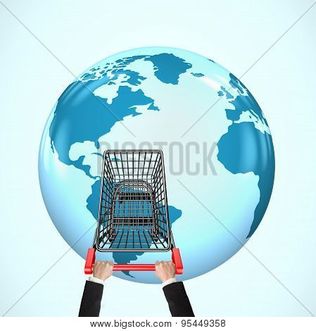 Hands Pushing Shopping Cart On 3D Globe With World Map