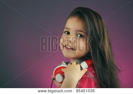 Beautiful little girl with headphones on colour background