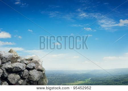 beautiful view of stones over green forest and glue sky