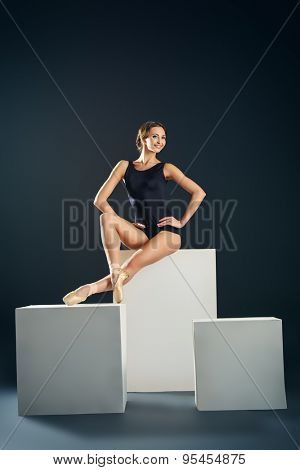Elegant beautiful ballet dancer in black ballet leotard posing at studio on white cubes. Art concept.