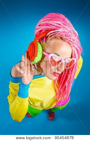 Ultra trendy DJ party girl in bright clothes, headphones and with bright dreadlocks. Disco, party. Show business. Bright fashion.