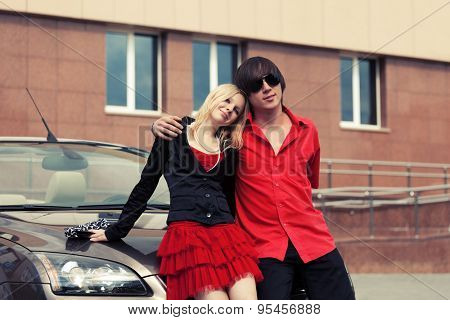 Happy young couple in love by convertible car