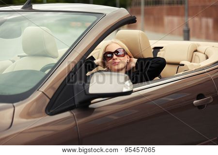 Young fashion woman in sunglasses in a convertible car