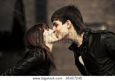 Happy young fashion couple in love kissing on city street