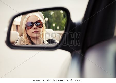 Blond fashion woman in sunglasses looking in the car rear view mirror