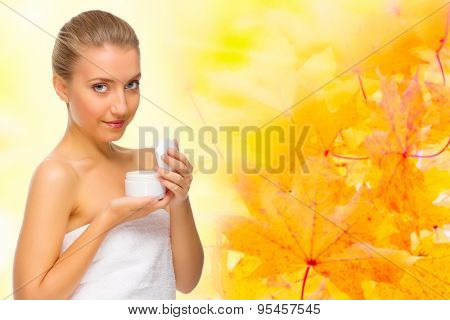 Young healthy girl with body cream jar on autumnal background