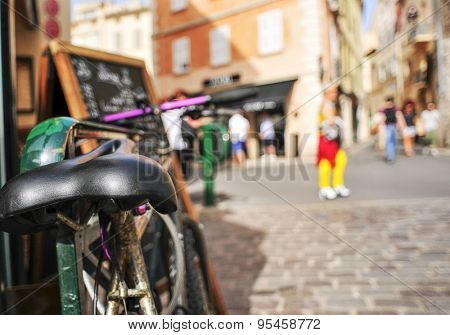 closeup of a worn-out bicycle in a pedestrian street in Saint-Tropez, France, with a filtered effect