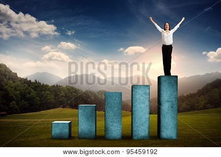 happy businesswoman winner standing on top of concrete diagram over beautiful landscape with forest, hills and sky