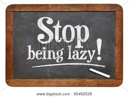 Stop being lazy sign - white chalk text on a vintage slate blackboard