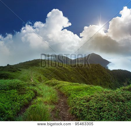 Summer landscape with footpath in the mountains. The sun breaks through the clouds