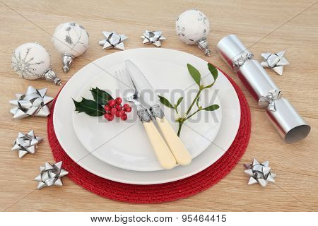 Christmas place setting with plates, cutlery, holly and mistletoe with baubles and cracker over light oak background.