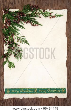 Background border with green merry christmas ribbon and cedar cypress on parchment over old oak wood.