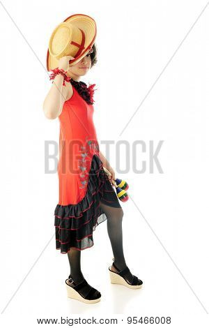 An attractive young teen tipping her hat in greeting while wearing a red and black Mexican dress and holding a pair of maracas.  On a white background.