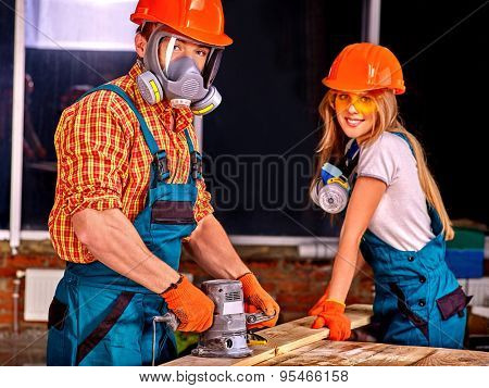 Man in gas mask and woman in builder helmet with electric planer.