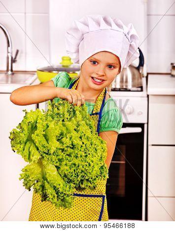 Child holding big green salad vegetable at kitchen.