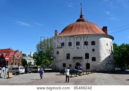VYBORG, LENINGRAD OBLAST, RUSSIA - JUNE 6, 2015: People at the Round tower on the market square. Built in in 1547-1550 as a part of the medieval town wall, now it serves as a restaurant