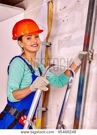 Woman in builder uniform on ladder  indoor.
