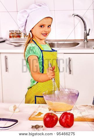 Child with rolling-pin dough at kitchen.Girl whisk eggs