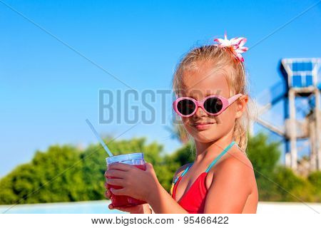 Child in glasses drinking soft drink near swimming pool.