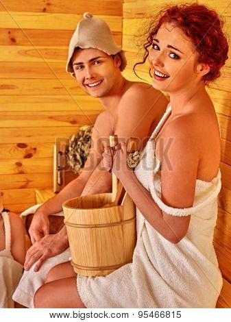 Couple man and woman wearing in hat  relaxing at sauna.