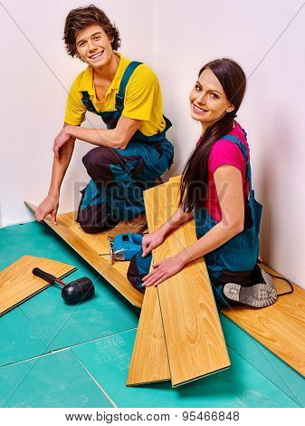 Happy family laying wooden parquet at home.
