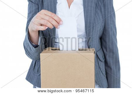 Businessman putting ballot in vote box on white background