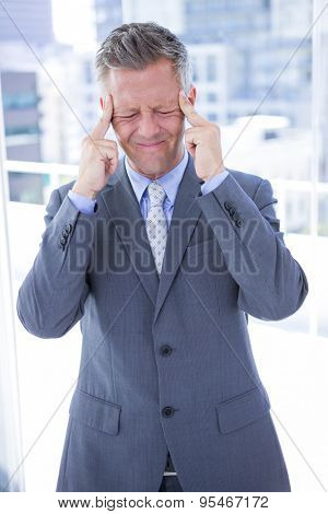 Businessman having a headache in the office