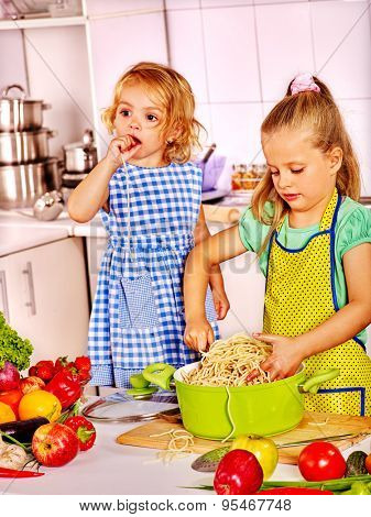 Children  girl eating spaghetti from pan at kitchen.