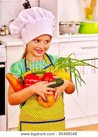 Child in cooking hat holding vegetable at kitchen. Little cook.