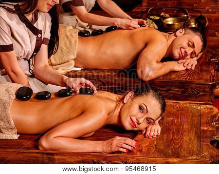 Couple  having stone oriental spa treatment. Two masseur.