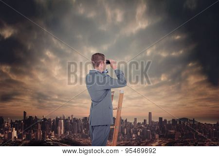 Businessman looking on a ladder against dusty path leading to large city