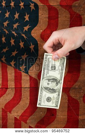 Hand holding hundred dollar bill against weathered oak floor boards background