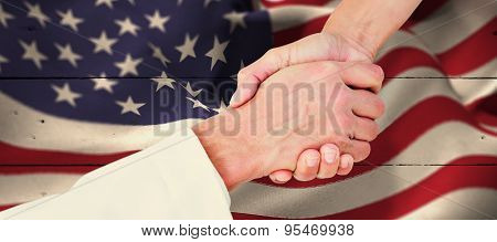 Extreme closeup of a doctor and patient shaking hands against white wood