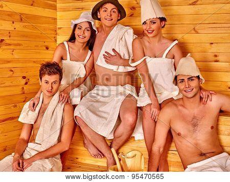 Group people men and women in hat  relaxing in sauna.