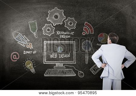 Serious businessman with hands on hips against black background