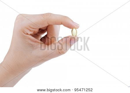 Woman's hand holding transparent yellow pill on white