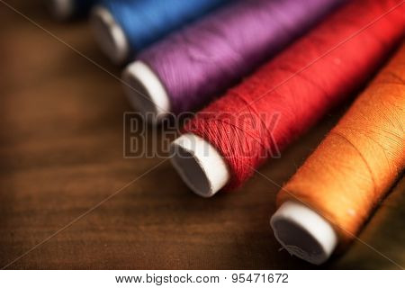 Colored sewing threads on a old work table with impressional feel., Extremely shallow depth of focus for dreamy feel.