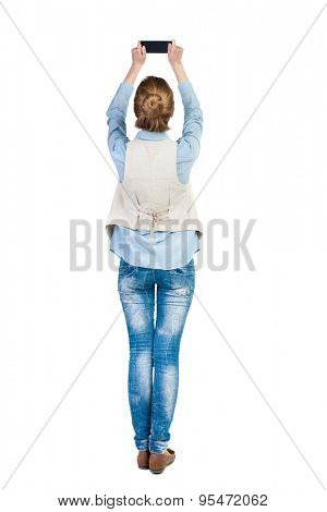 back view standing young beautiful  woman  in vest and using a mobile phone. girl  watching.  backside view person.  Isolated over white background. Girl in sleeveless photographs on top phone itself