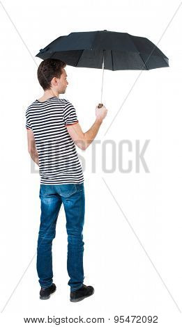 Back view of man in jeans under an umbrella. Standing young guy. Rear view people collection.   Isolated over white background. The guy in the striped shirt standing under a black umbrella.