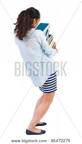 A girl carries a heavy pile of books. back view. Rear view people collection.   Isolated over white background. African-American woman in a denim shirt, trying to keep a stack of books.