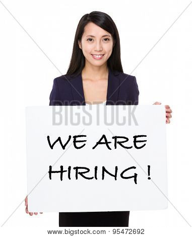 Confident businesswoman showing a placard showing with we are hiring phrases