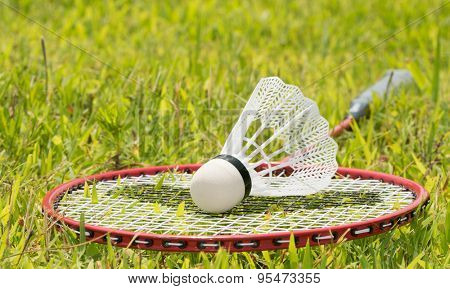 Badminton racquet with a shuttlecock on top in summer grass