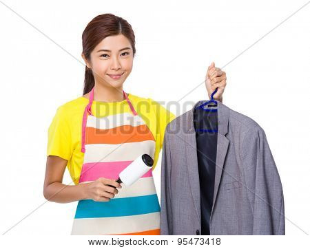 Young housewife using the duster on suit jacket