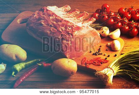 Raw Steak with vegetables on wooden board. Filtered image:cross processed vintage effect.
