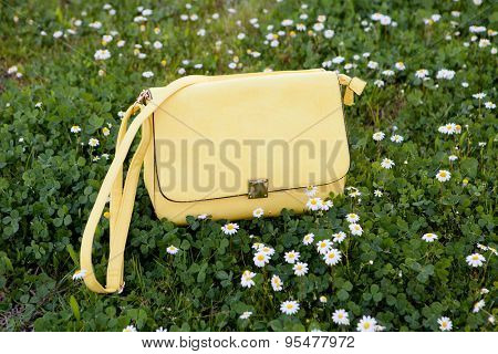 Fashion yellow bag on the grass surrounded by daisies