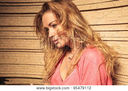 side view portrait of a beautiful young casual woman with nice hairstyle looking away from the camera