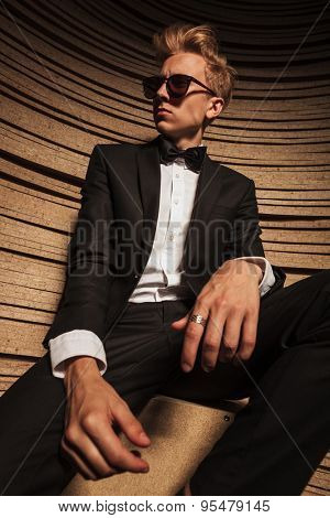 Down view of a young business man looking away while sitting on a chair.