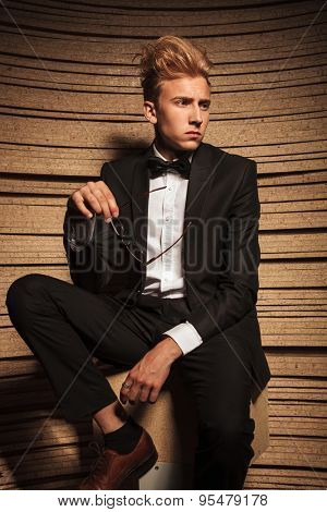 Blond young elegant man sitting on a chair while looking away from the camera.